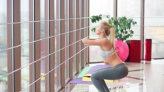 The girl squats in the gym Stock Footage