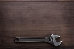 adjustable wrench on the wooden background - stock photo