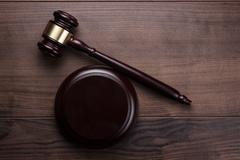 judge gavel on brown wooden background - stock photo