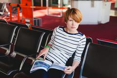 Woman reading newspaper at Charles de Gaulle airport, Stock Photos