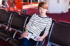 Woman reading newspaper at Charles de Gaulle airport Stock Photos