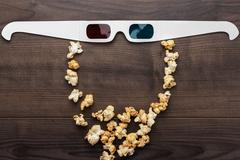 Anaglyph glasses and popcorn making bearded face Stock Photos