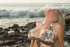 Woman in bikini at a rocky beach Stock Photos