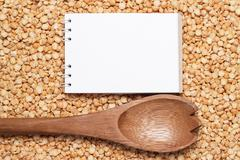 notebook and wooden spoon over peas background - stock photo