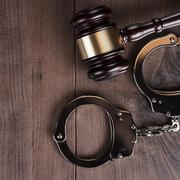 handcuffs and judge gavel on wooden background - stock photo