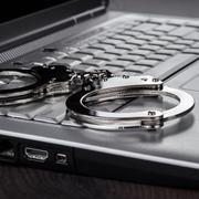 handcuffs on laptop cyber crime concept - stock photo
