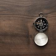 Compass on the brown wooden table Stock Photos