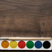 box of paints and a brush on the table - stock photo