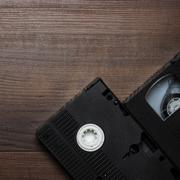 old retro video tape over wooden background - stock photo