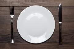 white plate with knife and fork on wooden table - stock photo