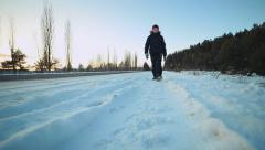 Snow-covered road. The child goes through the snow - stock footage