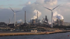 Climate Change - Wind turbines, track to a coal-fired power station chimney - stock footage