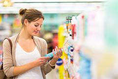 Beautiful young woman shopping in a grocery store/supermarket (c Stock Photos