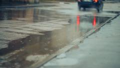 Rain. Cyclists and cars go through the puddles  Stock Footage