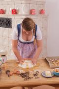 Young woman with deep cleavage kneads dough. Stock Photos