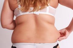 Woman pinches in the fat at the waist - stock photo
