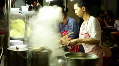 Steam rising as noodles are added by Asian man to pot on street food vendor cart Stock Footage