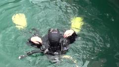 Diver in water puts on aqualungs Stock Footage