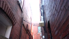 Narrow alley between red brick buildings Stock Footage
