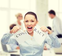 Stock Photo of serious businesswoman tearing contract