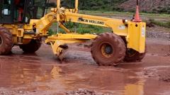 Grader on a flood road Stock Footage