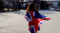 Camera To Girl, Wrapped In Union Jack Flag and turning around Stock Footage