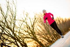 Young woman running outdoors on a cold winter day Stock Photos