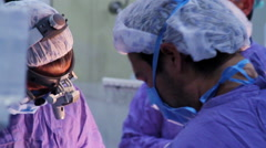 Mexico, 2014: CLOSE UP-BACK SHOULDER. Surgeons faces during surgery. - stock footage