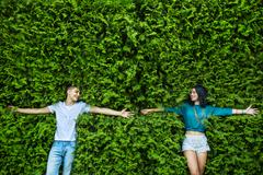 Young couple is closing his eyes back on the bright green foliag Stock Photos