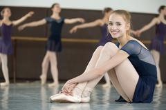 ballerina with smile sitting on the floor in a dance class - stock photo
