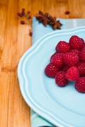 Bunch of raspberries on a ceramic blue plate on wood background. - stock photo