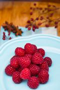 Bunch of raspberries on a ceramic blue plate on wood background. Stock Photos