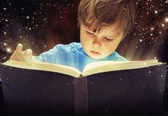 Amazed young boy with magic book - stock photo