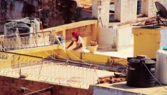 Construction worker on the rooftops of the blue city of Jodhpur, India Stock Footage
