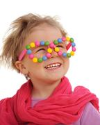 Portrait of cute little girl wearing funny glasses, decorated with colorful swee - stock photo