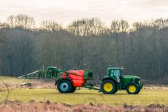 Fertilizing tractor a field - stock photo