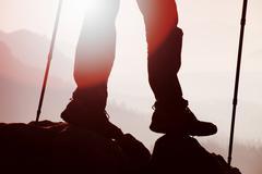 Man hiker legs  and poles stand on mountain peak rock Stock Photos