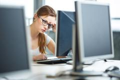 Pretty, female student looking at a desktop computer screen, lea Stock Photos