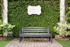 Wooden dark brown bench and blank vintage card against green lea - stock photo