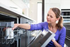 Housework: young woman putting dishes in the dishwasher Stock Photos