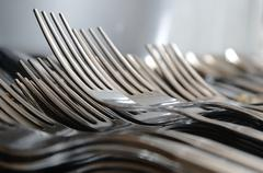 Forks arranged in series on the kitchen table. Stock Photos