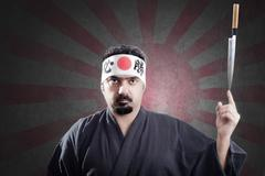 japanese style cook keeps a knife in equilibrium on a finger - stock photo