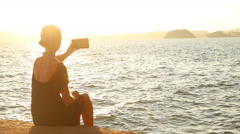 young blonde woman makes selfy at sunset against back light - stock footage