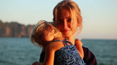 Blonde woman with small child admires sea sunset Stock Footage