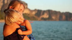 blonde woman with small child admires sunset against cliffs - stock footage