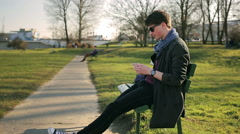 Student sitting on the bench in park and doing selfie on smartphone Stock Footage