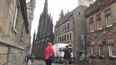 Castlehill street, road to Edinburgh Castle landmark, Asian tourists visiting Stock Footage