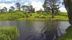 Hobbit holes behind lake Stock Footage
