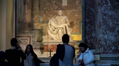 Tourists at the sculpture Pietà ( Michelangelo ) inside St. Peter's Basilica Stock Footage