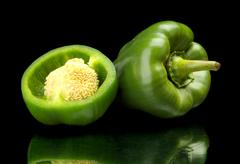 Studio shot of halved green bell peppers isolated on black background - stock photo